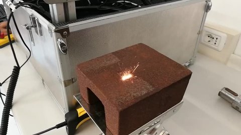 Italy July 2017 - Laser marking (10W power) of a QR code on a piece of crude steel