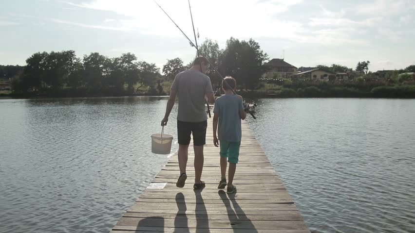 Father and son going fishing with rods on lake