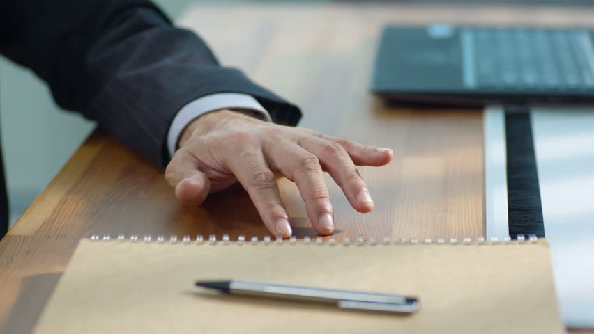 Fingers of a contemplative businessman tapping the surface of and drawing circles on desk. | Shutterstock HD Video #29565955