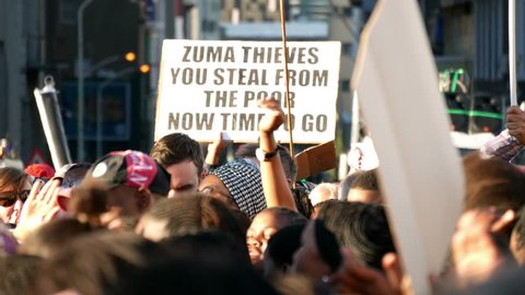 """CAPE TOWN SOUTH AFRICA, 7 AUGUST 2017, Jacob Zuma no confidence vote march to parliament """"Zuma Thieves placard above heads of raised hands hand clapping crowd"""