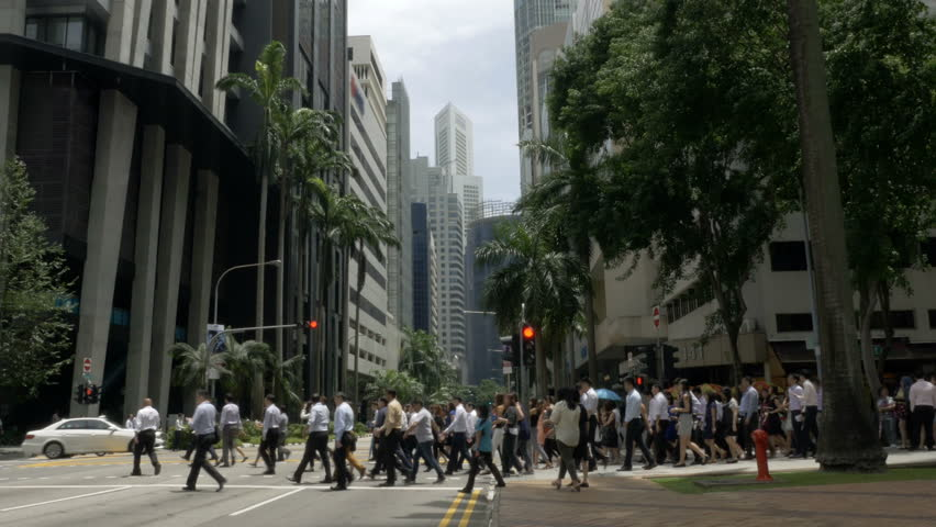 Crowd of business people crossing the street in downtown Singapore, Asia