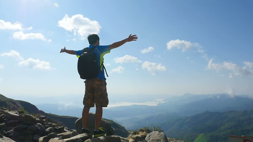 Cheering young man hiker open arms at mountain peak | Shutterstock HD Video #29587945