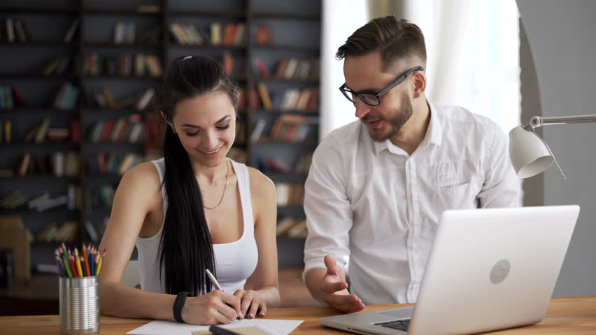 Two young startup partners together discuss and smile on wooden desk in hipster trendy loft. Male person explaining something to adult female. She is write on the white paper closeup | Shutterstock HD Video #29598175