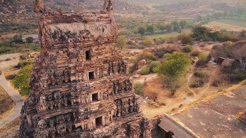 Flight over Sri Hanuman temple, Hampi, Karnataka, India. Amazing flinstones -like hills in the background