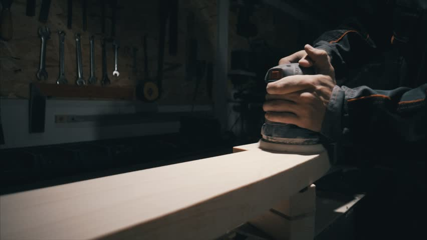 Close-up, woodworker grind piece of elm wood , to make it smoother, solid wood furniture manufacturing, low light