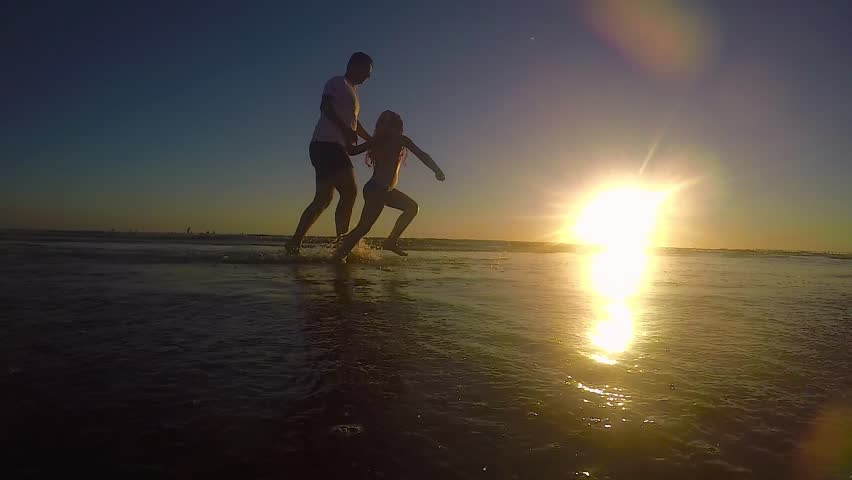 Father and daughter playing on the beach at the day sunset. Concept of friendly family. #29665435