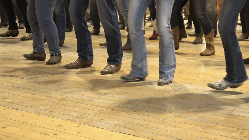 Cremona, Italy, May 2017 - People dancing bluegrass music, line dance at a folk event, cowboy USA style. Cowboy stepping choreography American horse festival. Tradition jeans boots and flag