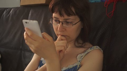 A young woman with glasses and a colorful nightdress sits on a leather black couch and uses a white smartphone