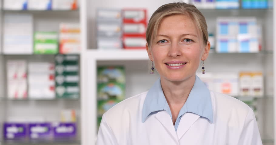 Closeup Of Smiling Pharmaceutist Woman Looking Camera, Thumb up Sign In Pharmacy Store