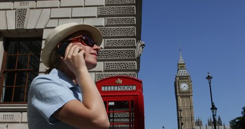 4K Woman talk at mobile phone near traditional red phone, Big Ben Tower in London