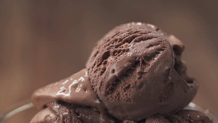 Slow motion of chocolate flakes falling on chocolate ice cream