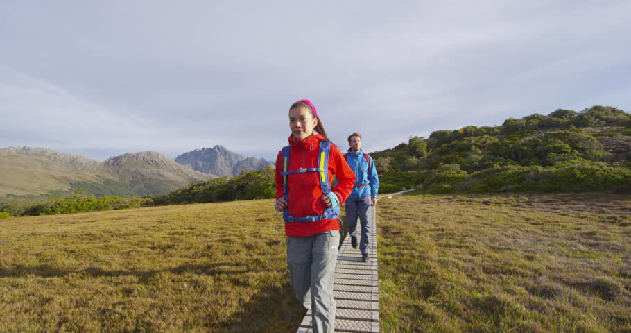 Young hiking couple walking on adventure in New Zealand on boardwalk at famous Routeburn Track. Hikers carrying backpacks tramping Key Summit Track on vacation at Fiordland National Park, New Zealand.