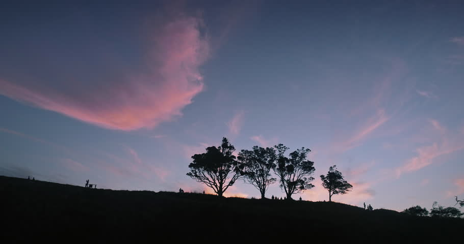 Aerial Silhouette of people walking on a Mt Eden volcano ridge at stunning epic sunset. The clouds are whispy and the trees are pohutukawa. Auckland, New Zealand