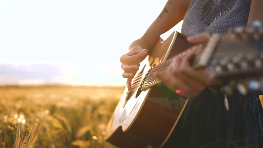 Girl's hands playing guitar at wheat field