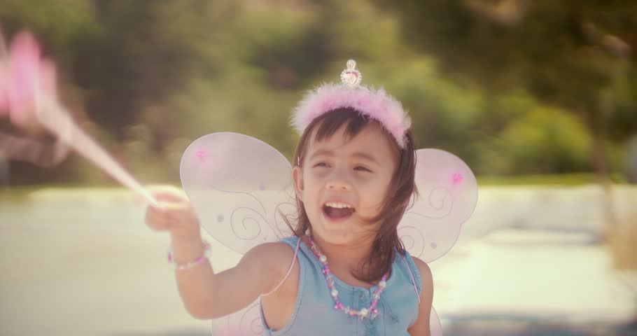 Cheerful little Asian girl in pink fairy queen costume playing make-believe in park in summer