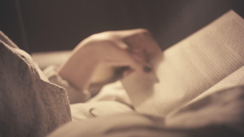 Young woman reading old book in bed at late night. Indoors interior background.