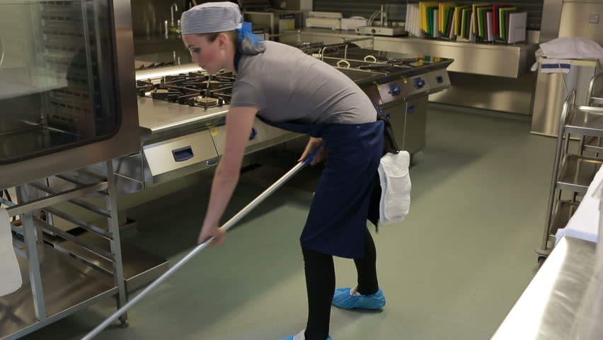 cleaner cleaning the kitchen and wiping the floor with a mop stock