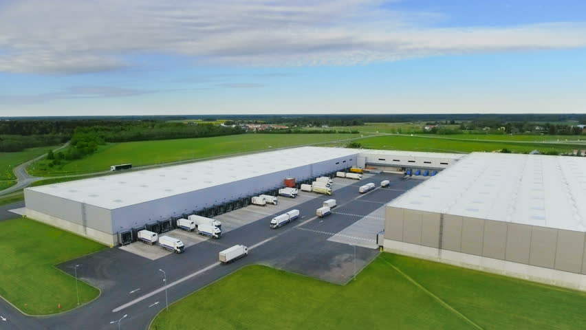 Aerial Shot of Industrial Warehouse/ Storage Building/ Loading Area where Many Trucks Are Loading/ Unloading Merchandise. Shot on Phantom 4K UHD Camera.