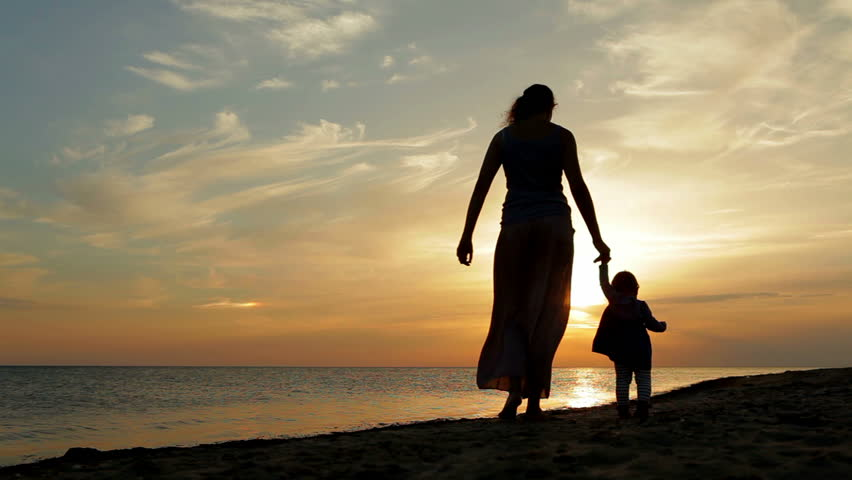 Mother with baby walking on sea coast. Silhouettes sunset. | Shutterstock HD Video #2980060