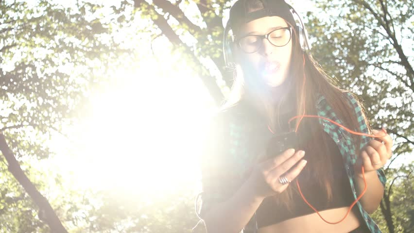Hipster girl listening to music off her smartphone on a sunny spring day. | Shutterstock HD Video #29808625