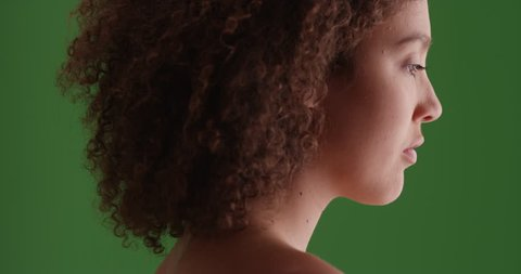 Black girl looks on green screen. On green screen to be keyed or composited.