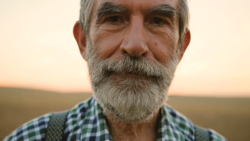 Close up portrait of happy fermer with beard smiling on camera in the golden field on the sky background. #29822365