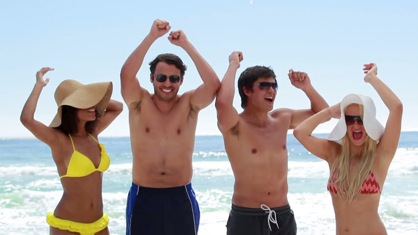 Four friends partying together on the beach while on holidays