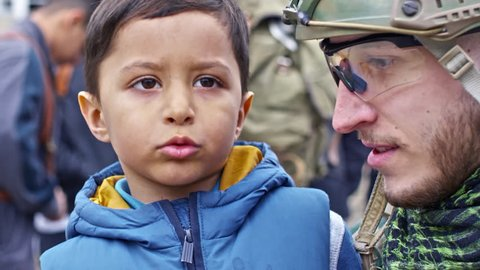 Tilt up of cute Syrian refugee boy holding plush toy and telling story to laughing Caucasian soldier in protective helmet and glasses