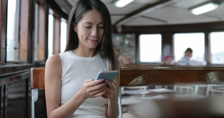 Woman using cellphone on ferry in Hong Kong
