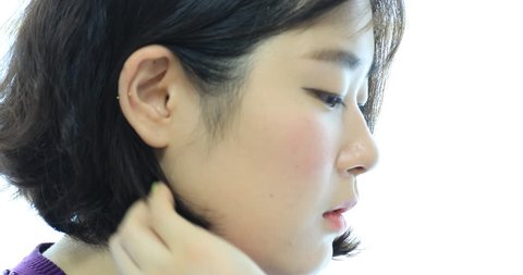 Beautiful young asian woman running her fingers through her hair to show  her ear