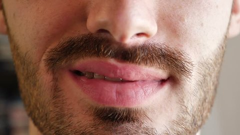 Close-up of young man lips and mouth, with mustache and goatee. Unshaved face