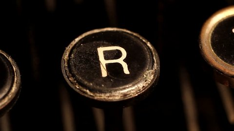 "A male finger presses the letter ""R"" key on an old typewriter."