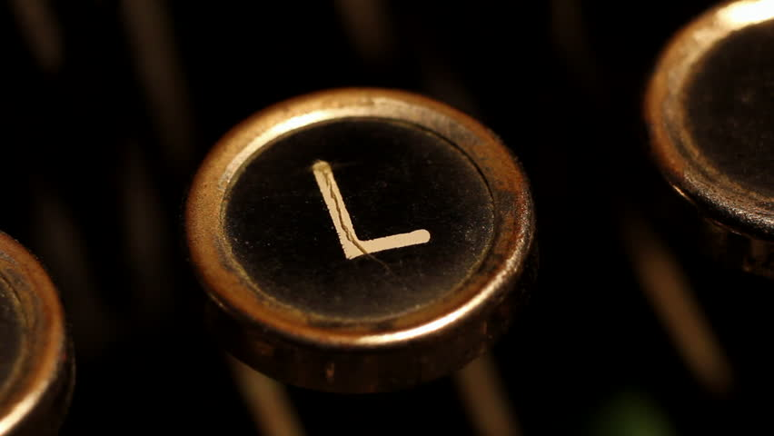 "A male finger presses the letter ""L"" key on an old typewriter."