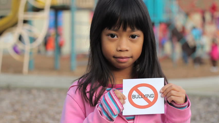 A cute Asian girl holds up a small NO BULLYING sign on the school playground.