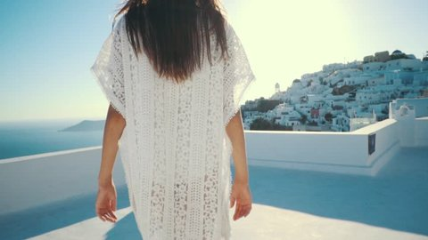Young sexy woman is on the greek island Santorini in a white dress and and straw hat white greek houses volcano sea sunny weather