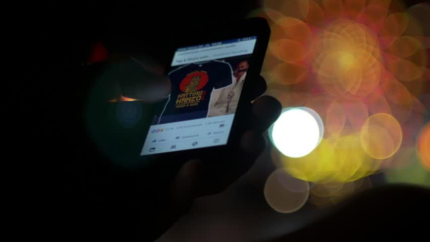 NESSEBAR, BULGARIA, AUGUST 2017, Social network facebook app browsing on smartphone at night