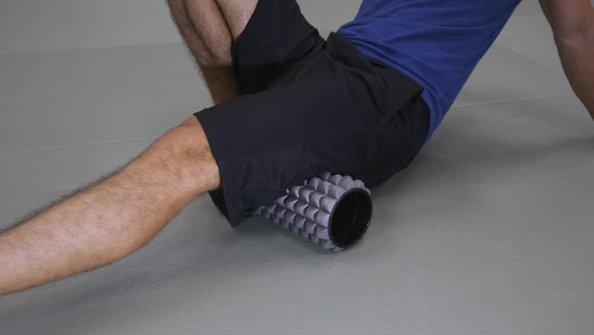 Detail of athletic young man using a foam roller to roll out thigh muscles.  | Shutterstock HD Video #29920285