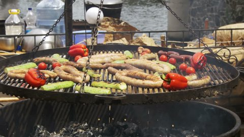 Cooking Barbecue Delicious and Vegetables on the Grill. Browned Sausages, chicken, bell pepper, eggplant, tomatoes are fried on a barbecue. Outdoor cooking.
