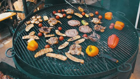 Cooking of Meat and Vegetables on the Grill. Barbecue delicious, Browned Sausages, chicken, bell pepper, eggplant, tomatoes are fried on a barbecue. Outdoor cooking.