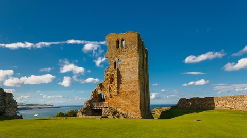 POV gimbal shot towards the medieval Scarborough Castle during sunset golden hour against a bright blue sky, Yorkshire, England, UK
