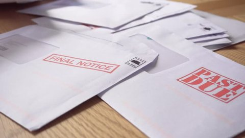 Debt Letters Piling Up with Bills Overdue, Past Due and Final Notice. Red Writing to Represent Economic Struggle, Unemployment, Home Repossession and Recession,