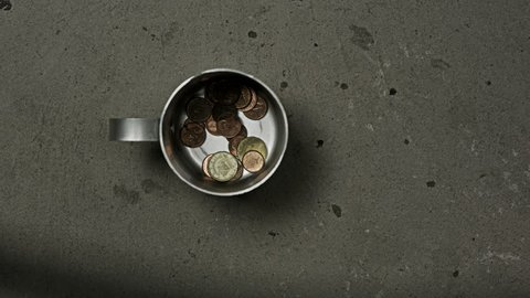 beggar's mug being filled with coins and dollar