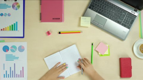 Person writing to do list at work, self employed woman planning a day, startup. Top view of female hands working, writing down in notebook