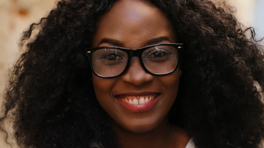 Close up portrait of beatiful curly hair african woman in the glasses smiling on the camera on the street background.