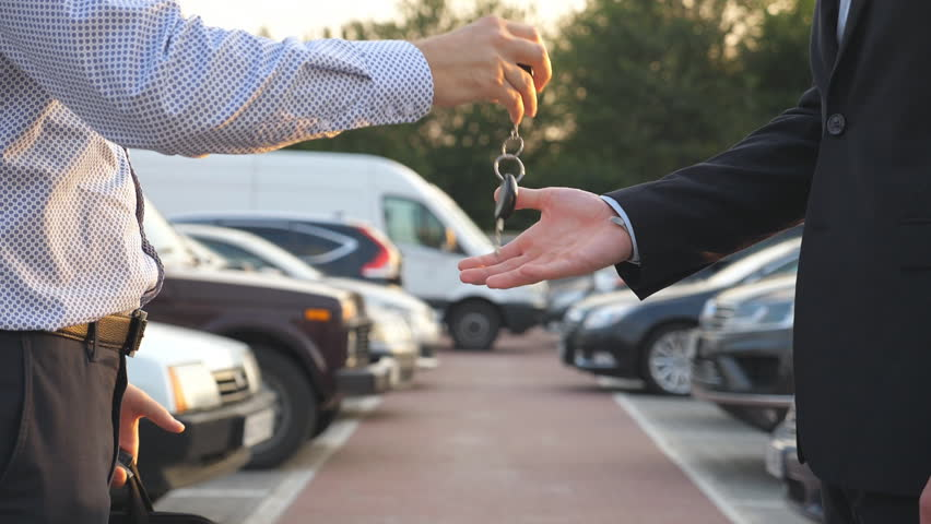 Male hands in suit giving keys of car to his friend. Arm of businessman passes car key. Handshake between two business men outdoor. Close up Slow motion