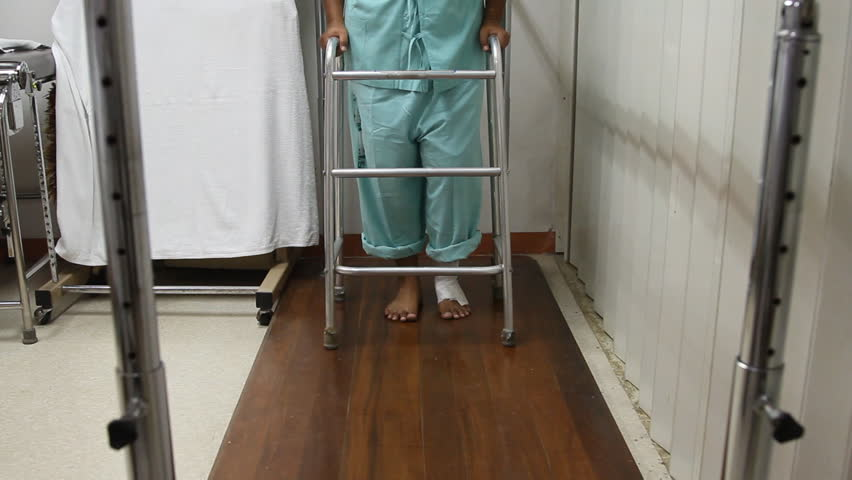 Low section of woman with walker and training on wooden floor