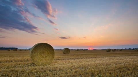Stubble field with straw bales under sunset sky with colorful clouds. 4k timelapse 3840x2160