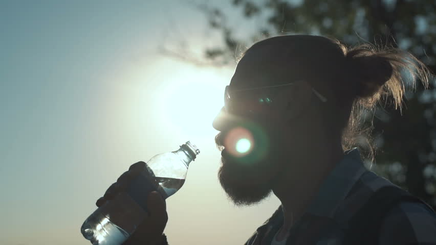 Slow motion shot of side view of stylish man with ponytail drinking water from bottle on background of sunlight and nature.