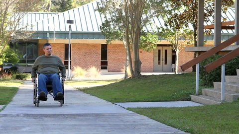 Overweight veteran paraplegic man in wheelchair pushes himself up an  inclined sidewalk rolling at a state university