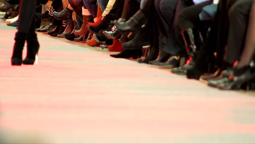 Legs models walking down the catwalk. Show on the catwalk. Fashion show. Blurred silhouettes.